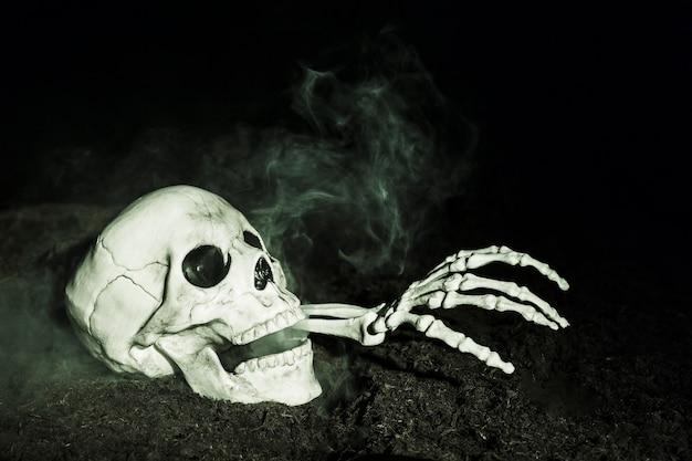 Mano de esqueleto que sale de la calavera en el suelo