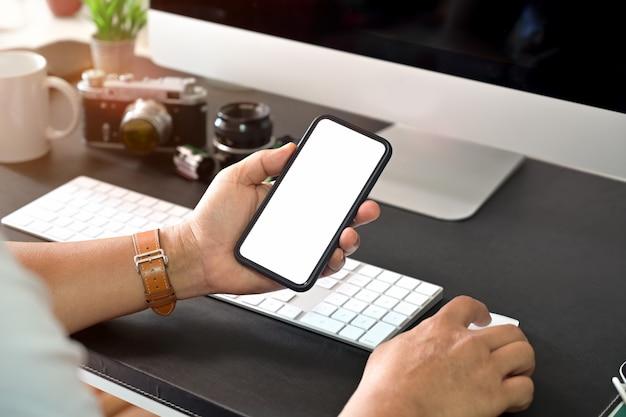 Mano con estilo creativo que sostiene el teléfono móvil de pantalla en blanco