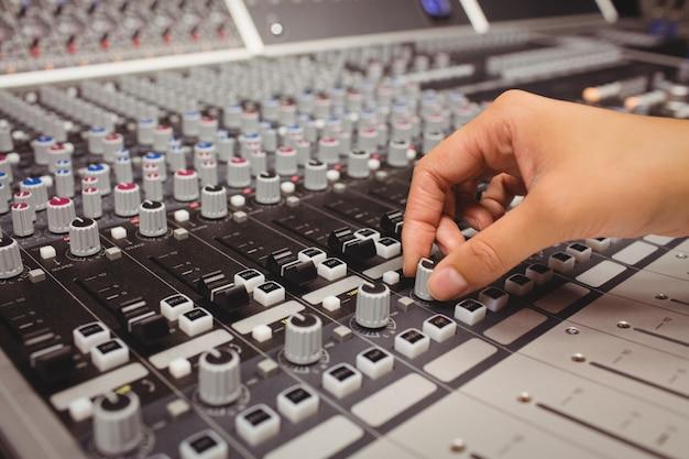 Mano de una estudiante con mezclador de sonido