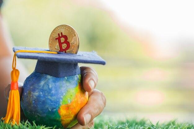 Mano de estudiante que cae invirtiendo la moneda de dinero bitcoin al fondo de graduación