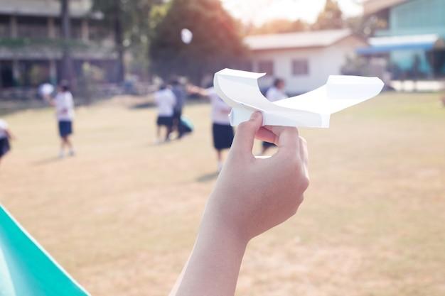 Mano del estudiante que sostiene el aeroplano de papel en clase de la educación del tronco.