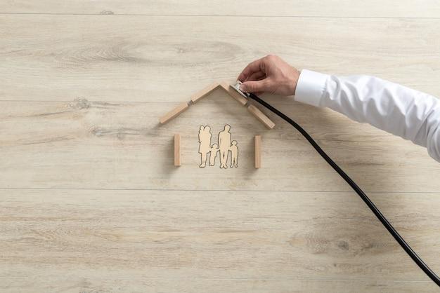 Mano de un experto sosteniendo un estetoscopio en el techo de una casa familiar.