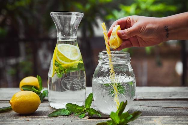 Mano exprimiendo limón en un frasco de vidrio con vista lateral del agua en la mesa de madera y jardín