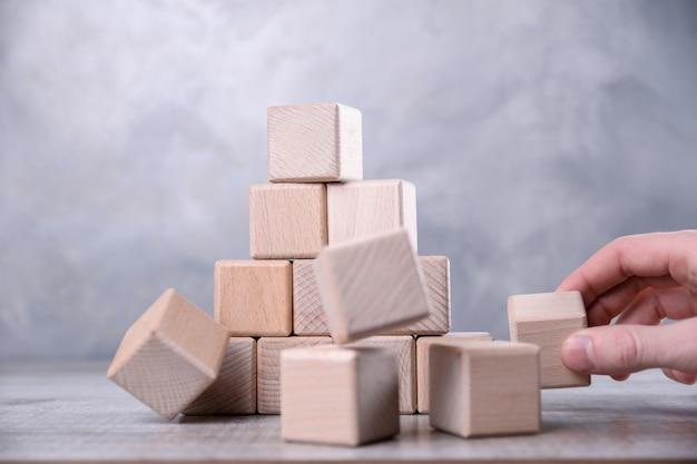 Mano extrae el cubo de madera en blanco con espacio para su palabra, letra, símbolo sobre la mesa. la influencia de una persona en el equipo. lugar para el texto, espacio de copia libre