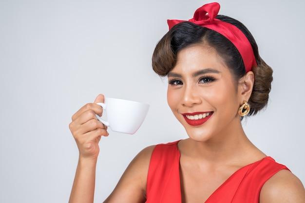 Mano feliz de la mujer de la moda que sostiene la taza de café
