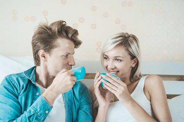 Mano feliz de los pares que sostiene la taza y que bebe el café por la mañana