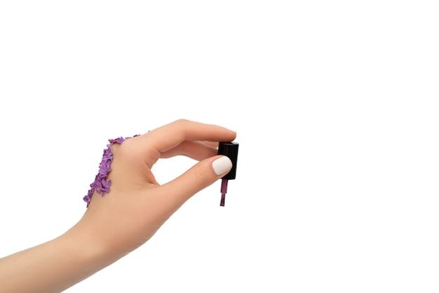 Mano femenina adornada con las flores de la lila que sostienen el cepillo púrpura del esmalte de uñas aislado en el fondo blanco. concepto de primavera.