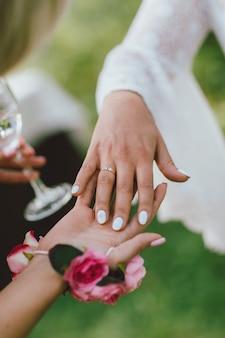 Mano femenina con anillo de bodas, damas de honor