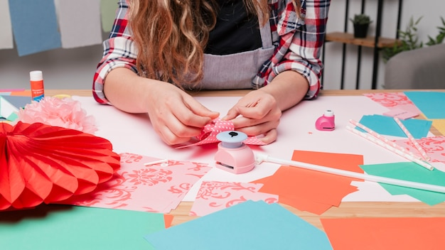 Mano femenina del artista que hace el molinillo de viento usando el papel del origami