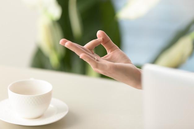 Mano femenina en la barbilla con gesto yogic
