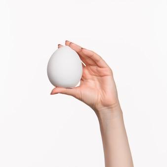 Mano femenina blanca ovalada de espuma de poliestireno en blanco
