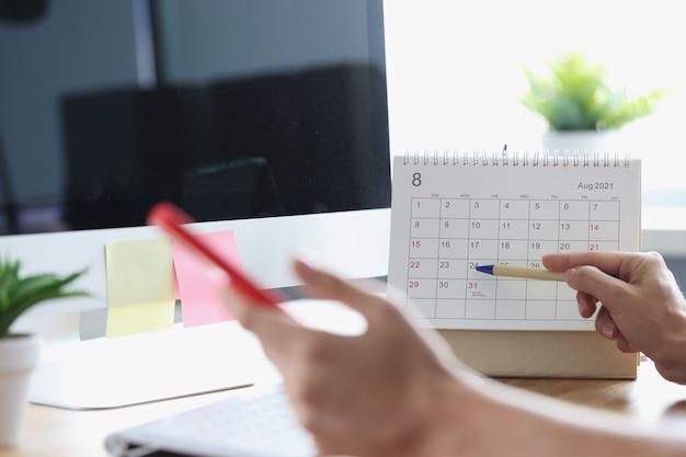 En mano femenina, un bolígrafo de teléfono inteligente con calendario en el concepto de planificación de procesos de negocio en el lugar de trabajo