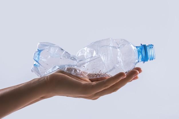 Mano femenina con una botella de plástico usada. concepto de contaminación de la tierra y principios de zero waste.