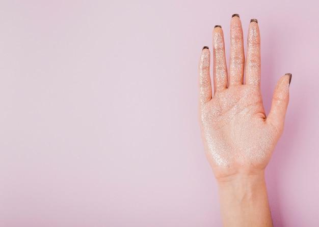 Mano femenina con brillo y copia espacio fondo rosa