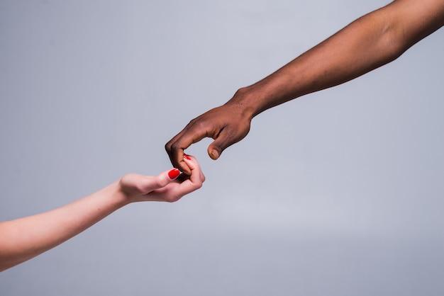 Mano femenina caucásica blanca y mano masculina negra sosteniendo los dedos juntos