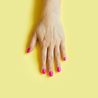 Mano femenina con uñas de color rosa sobre amarillo.