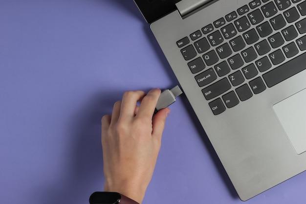 Mano femenina conecta la unidad flash usb a la computadora portátil en papel violeta