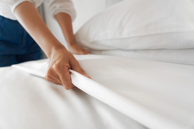 Mano femenina configurar sábana blanca en el dormitorio