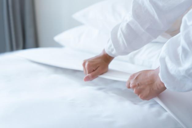 Mano femenina configurar sábana blanca en dormitorio