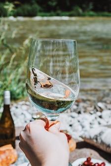 Mano femenina con copa de vino blanco en la costa del río y fondo de picnic romántico