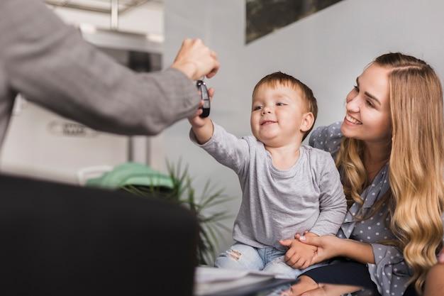 Mano femenina dando las llaves del auto a un bebé