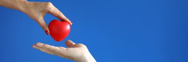 Mano femenina dar corazón rojo a la mano masculina sobre fondo azul closeup