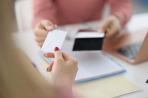 Mano femenina dar tarjeta de visita en blanco visitante socios de cuello blanco intercambio de nombre de empresa y