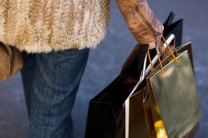 Mano femenina de la cosecha que sostiene bolsos de compras