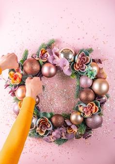 Mano femenina decoración hermosa corona de navidad inusual. aplanada
