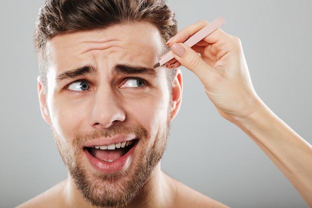Mano femenina depilando las cejas de los hombres asustados