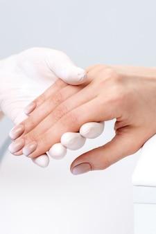 Mano femenina después de la manicura en la mano del maestro de manicura en el salón de uñas