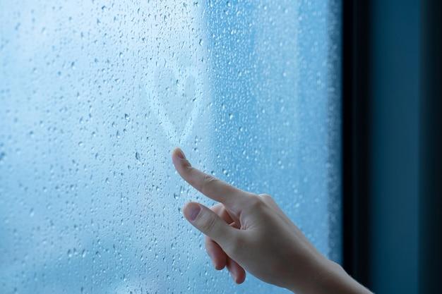 Mano femenina dibuja un corazón en una ventana con niebla durante la lluvia. vaso en gotas de agua. el concepto de romance.