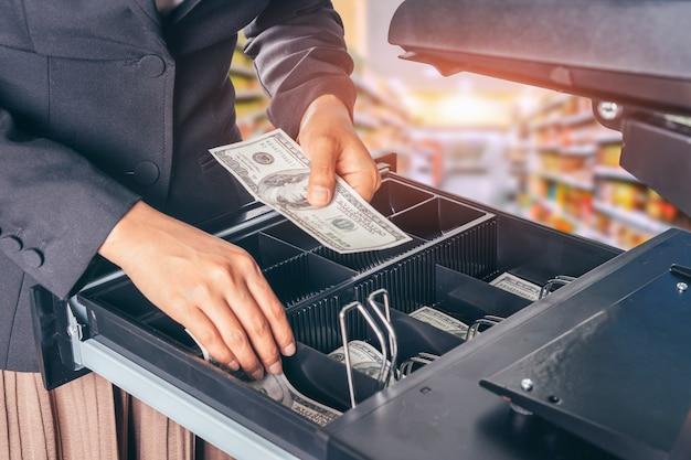 Mano femenina con dinero en tienda de supermercado.