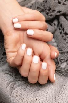 Mano femenina con diseño de uñas blanco, de cerca.