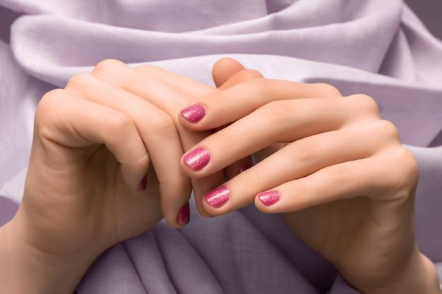 Mano femenina con diseño de uñas glitter rosa.