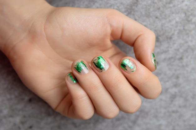 Mano femenina con diseño de uñas de lámina verde