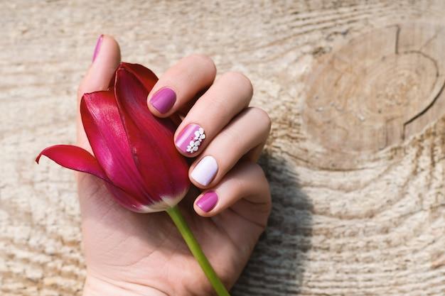 Mano femenina con diseño de uñas púrpura con hermoso tulipán rosa.