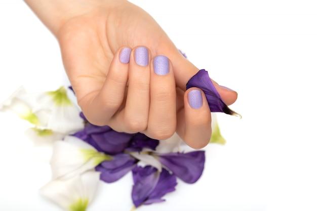 Mano femenina con diseño de uñas púrpura sobre fondo blanco.
