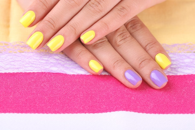Mano femenina con elegantes uñas de colores, en brillante