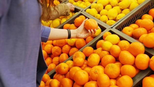Mano femenina elige naranjas cítricas y limones en la tienda