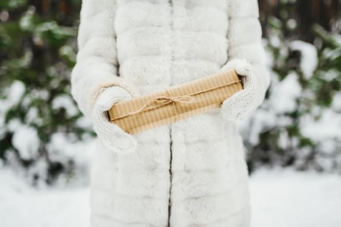 Mano femenina en un mitones de punto blanco con caja de regalo presente