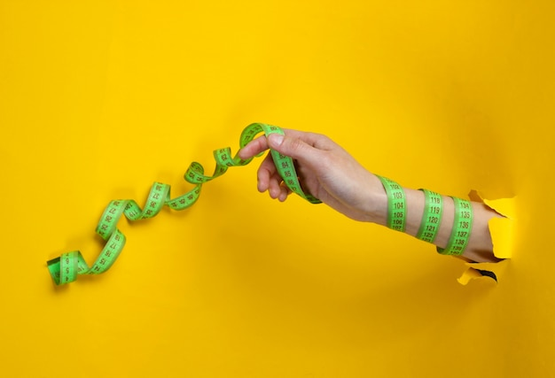 Mano femenina envuelta en una regla a través de papel amarillo rasgado. concepto de pérdida de peso minimalista