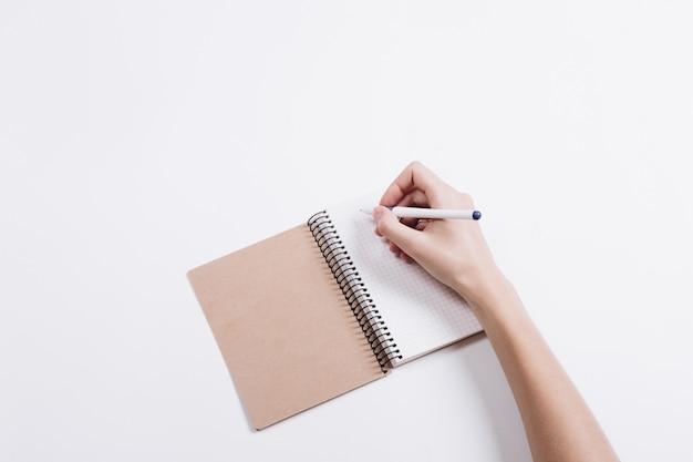 Mano femenina escribe una pluma en un cuaderno en una mesa blanca