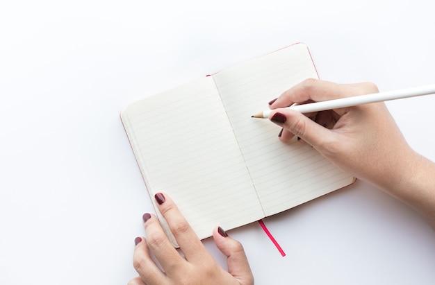 Mano femenina escribiendo en el bloc de notas ideas de conceptos de ideas e inspiración