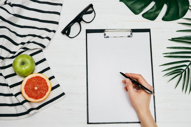 Mano femenina escribiendo texto en bloc de notas. estilo de vida o concepto de negocio.