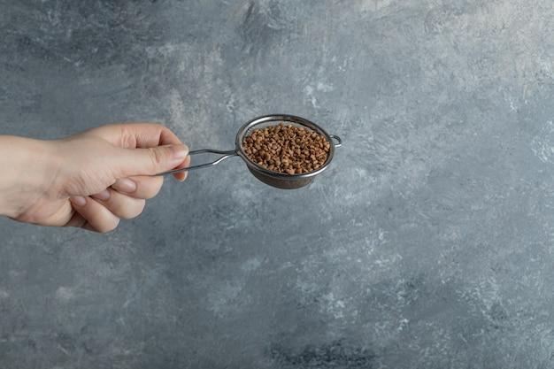 Mano femenina filtrando trigo sarraceno crudo con colador