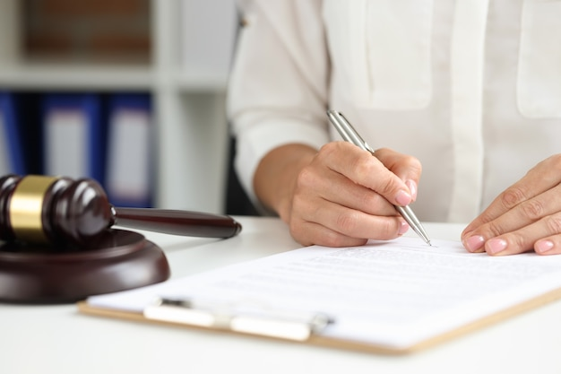 La mano femenina firma un acuerdo cerca de la decisión final del mazo del juez de madera del tribunal