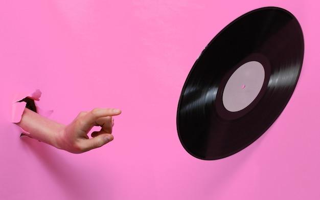 Mano femenina gira disco de vinilo a través del fondo de papel rosa rasgado. concepto retro minimalista