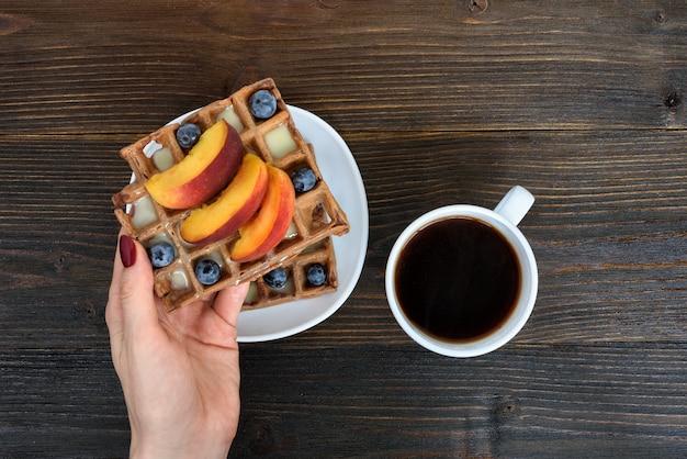 Mano femenina con gofres belgas con frutas y bayas. taza de cafe. fondo de madera vista superior