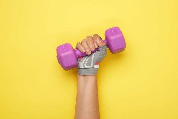 Mano femenina en un guante deportivo rosa sostiene una pesa de un kilogramo de color púrpura sobre una superficie amarilla